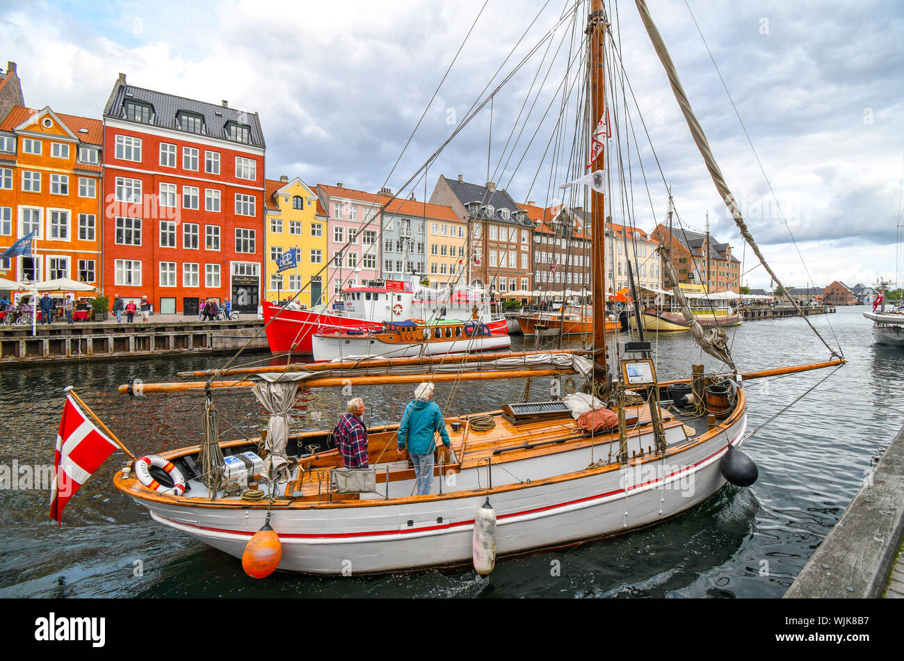 A senior man and woman dock their sailboat on the canal on an overcast day in the colorful 17th century Nyhavn district in Copenhagen, Denmark. Stock Photo
