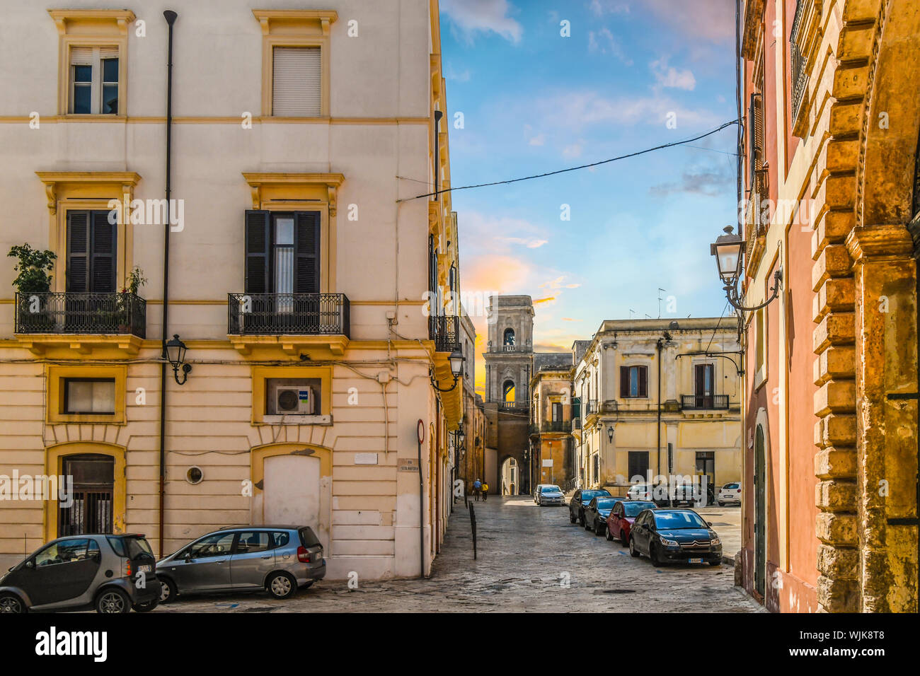 A couple is seen in the distance as they near a medieval church tower in the historic residential district of Brindisi, Italy. Stock Photo