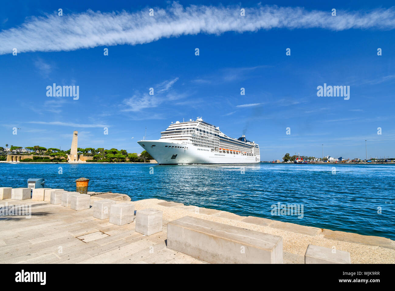 A massive cruise ship pulls into the narrow port on the Adriatic Sea in the mediterranean city of Brindisi, Italy, in the Puglia region. Stock Photo