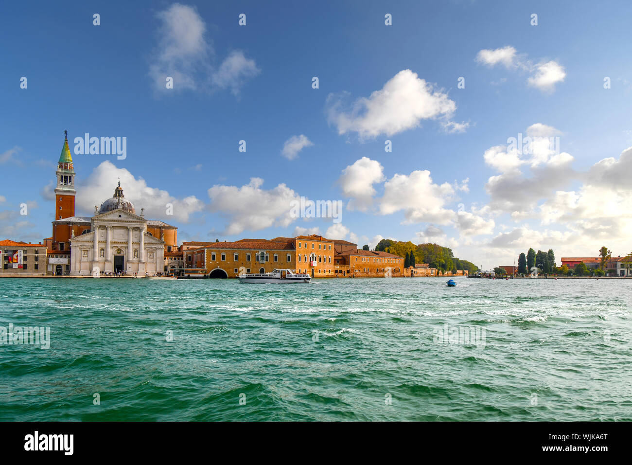 A small boat passes in front of San Giorgio Maggiore, the 16th century Church and tower on the island of San Giorgio Maggiore, in Venice, Italy. Stock Photo