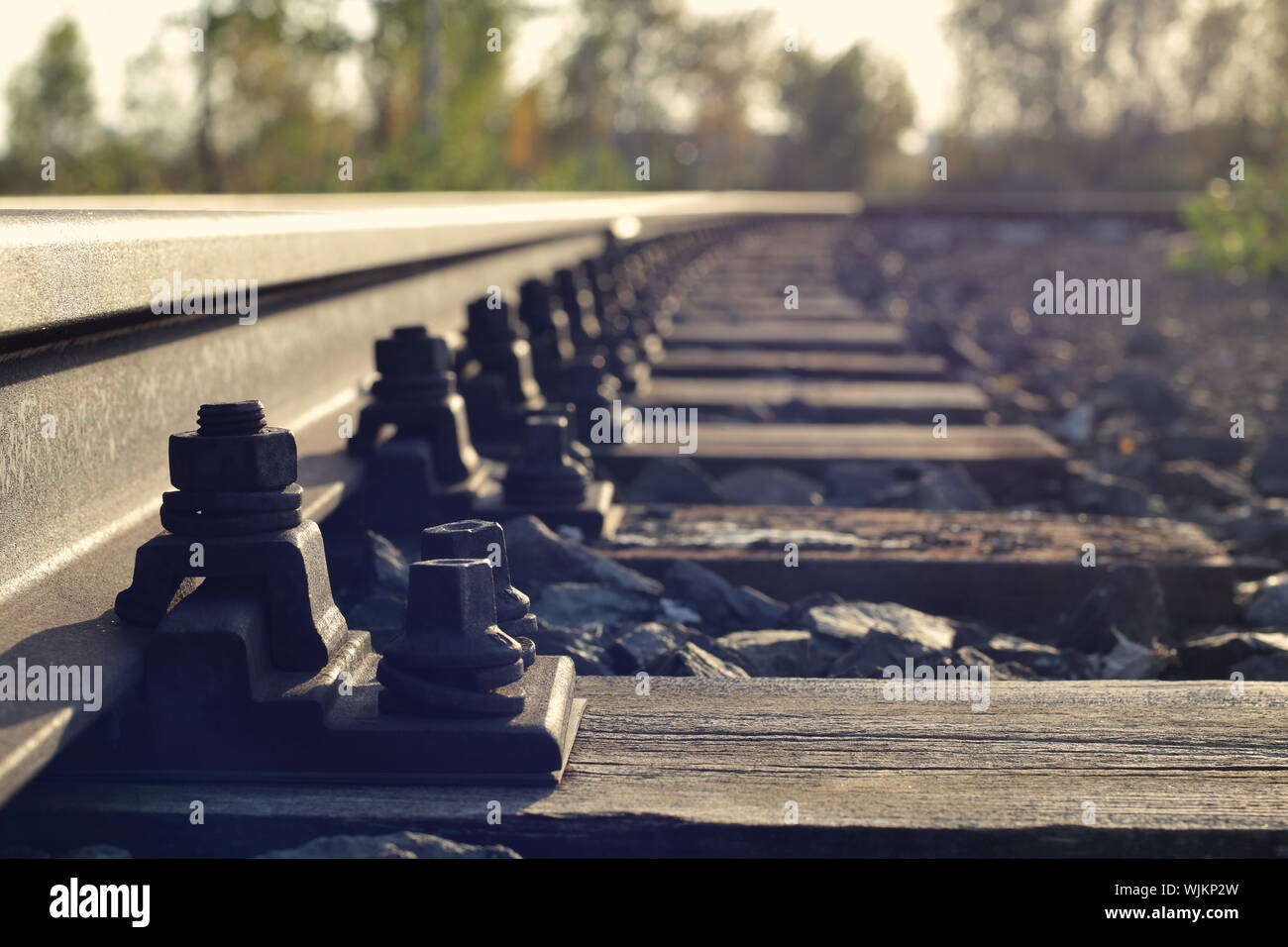 close-up of abandoned rusted rail with nuts, bolts and weathered wooden sleepers Stock Photo