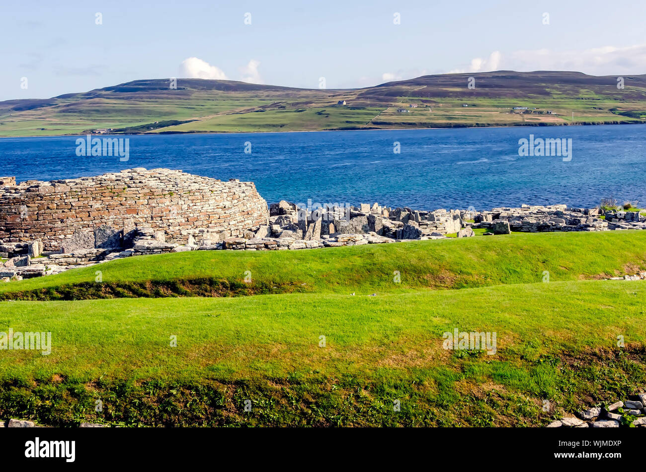 Broch of Gurness flanked by earth banks reinforced by stone. The broch village ruins surround it. - Stock Photo