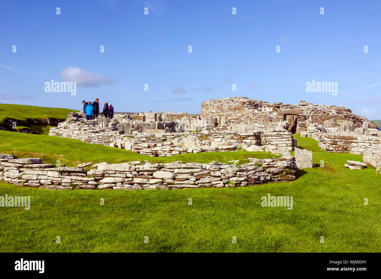 Broch of Gurness flanked by earth banks reinforced by stone. The broch village ruins surround it. Stock Photo