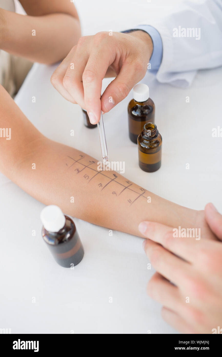 Closeup of doctor dropping medicine on hand of woman in clinic - Stock Photo
