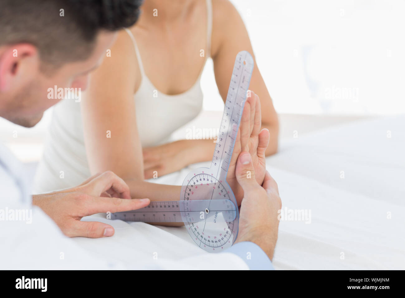 Physiotherapist examining patients wrist with goniometer in clinic Stock Photo