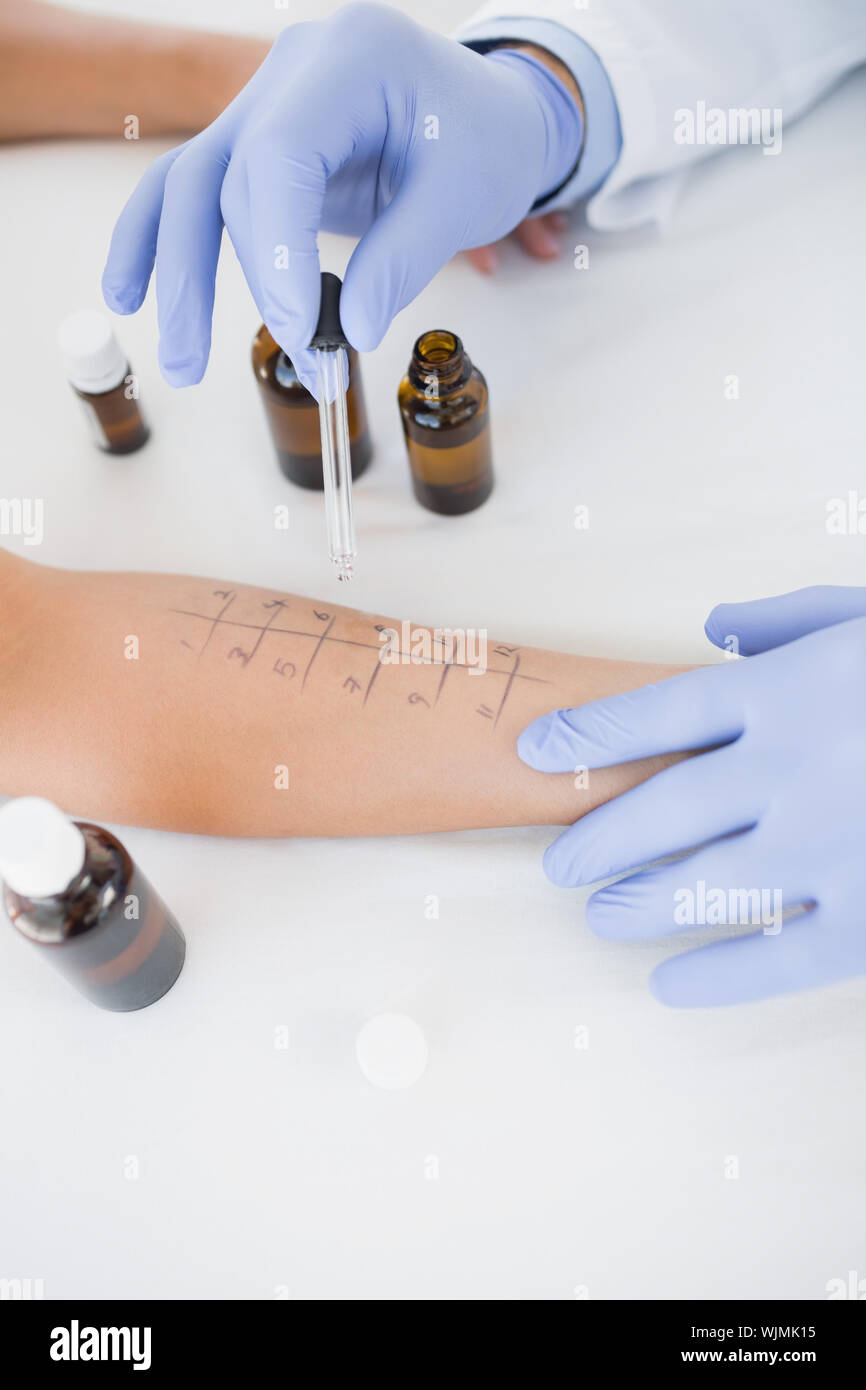Closeup of doctor dropping medicine on hand of patient in hospital - Stock Photo
