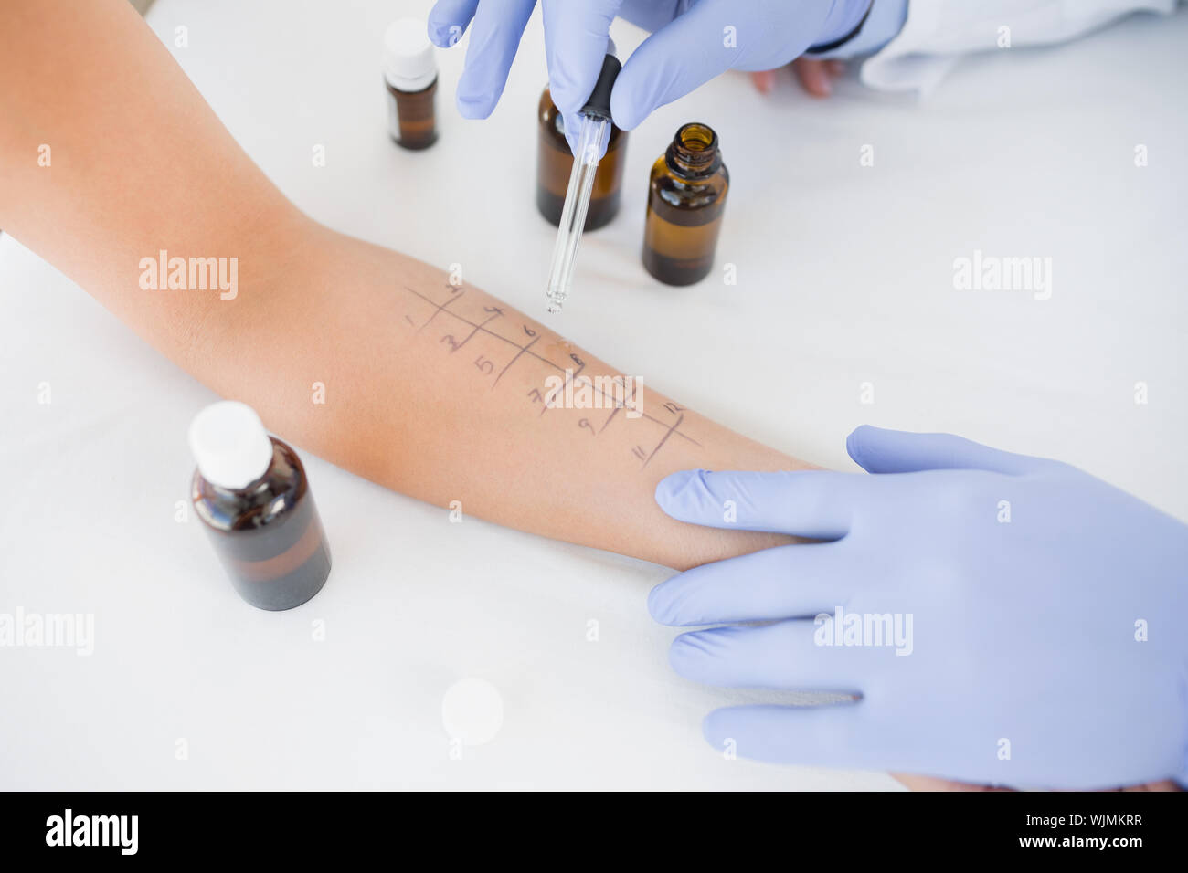 Closeup of doctor dropping medicine on hand of patient in clinic - Stock Photo