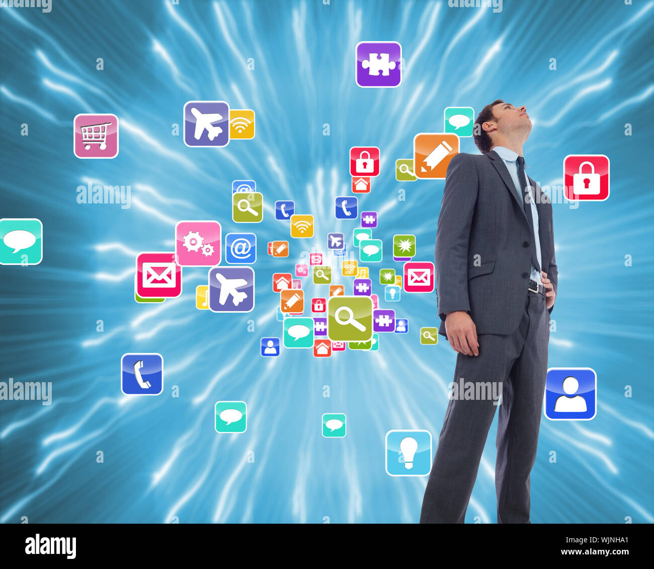 Serious businessman with hand on hip against strands of blue lights Stock Photo