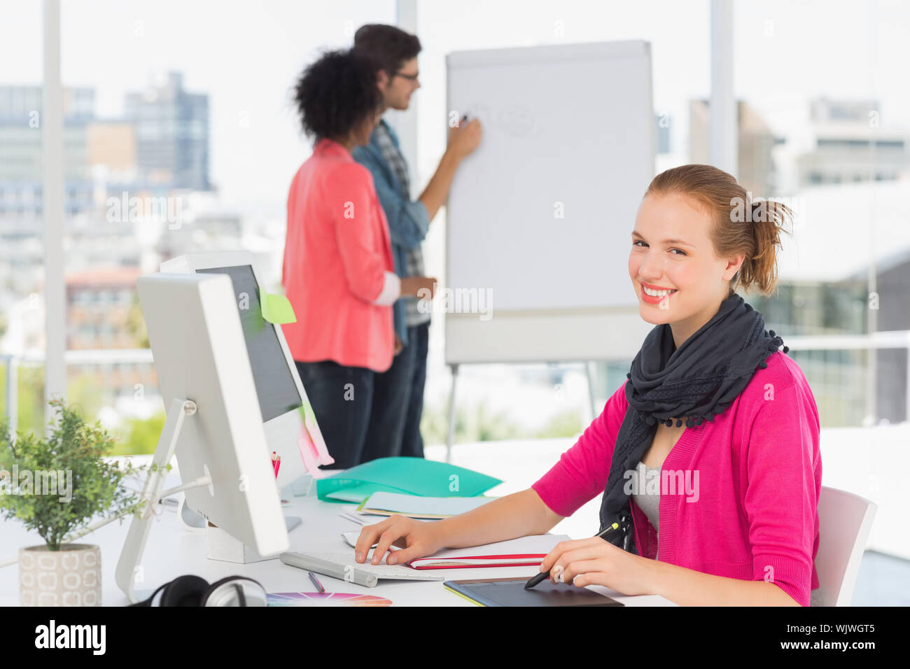 Portrait of a female artist using graphic tablet with colleagues behind at the office Stock Photo