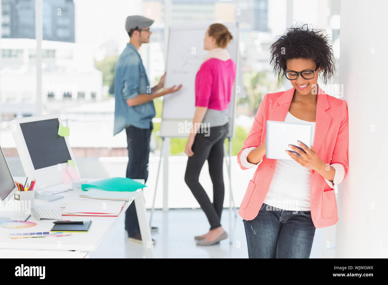 Casual female artist using digital tablet with colleagues in the background at a bright office Stock Photo
