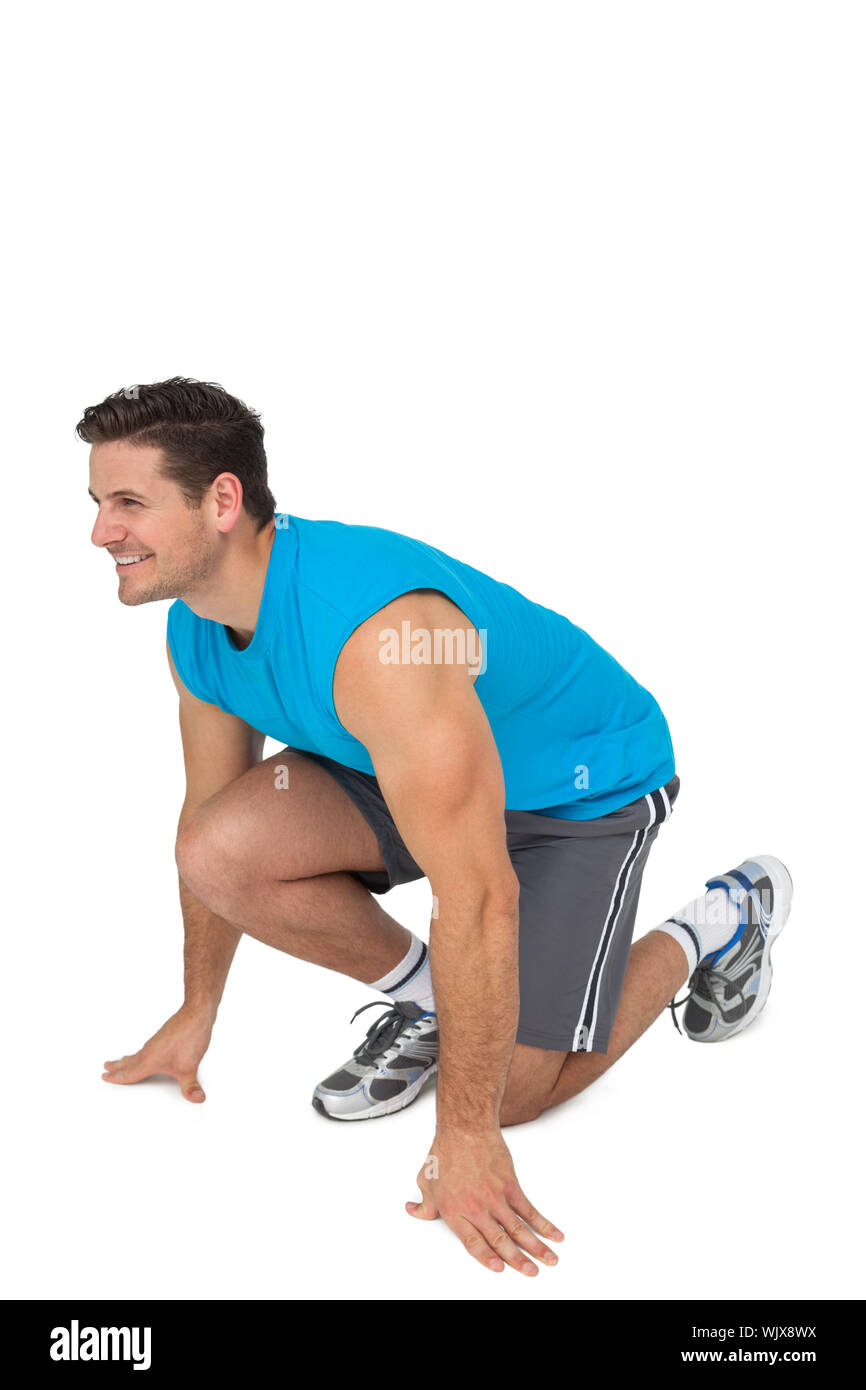 Side view of a young sporty smiling man in running stance over white background Stock Photo
