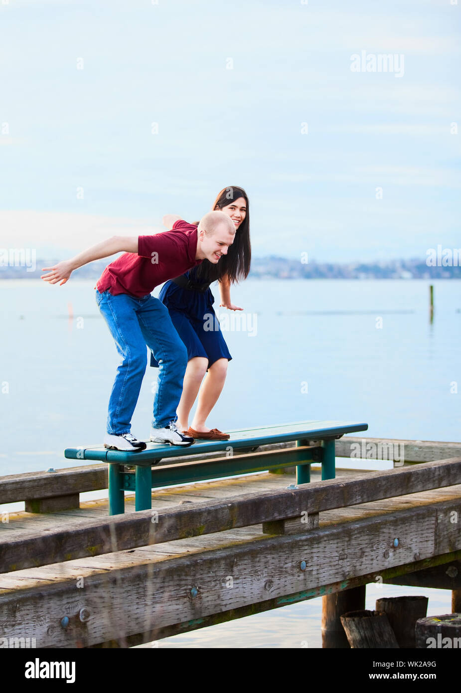 Happy young interracial couple  preparing to jump off  dock over lake, playful Stock Photo