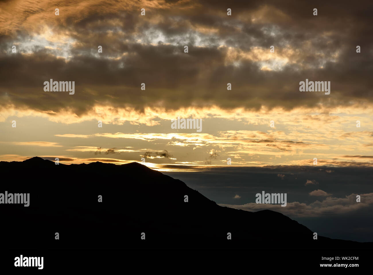 Amazing golden sunrise with the contours of the mountains in the first rays of sunlight against the backdrop of beautiful illuminated clouds in the sk - Stock Photo