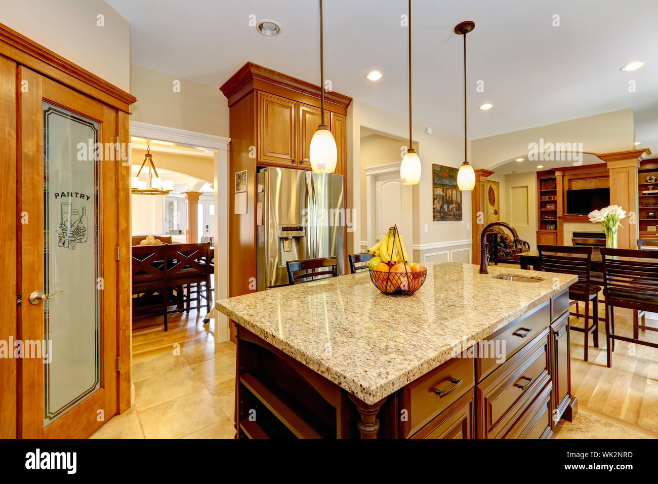Luxury kitchen with light brown  cabinets, steel appliances, pantry, marble counter top island Stock Photo