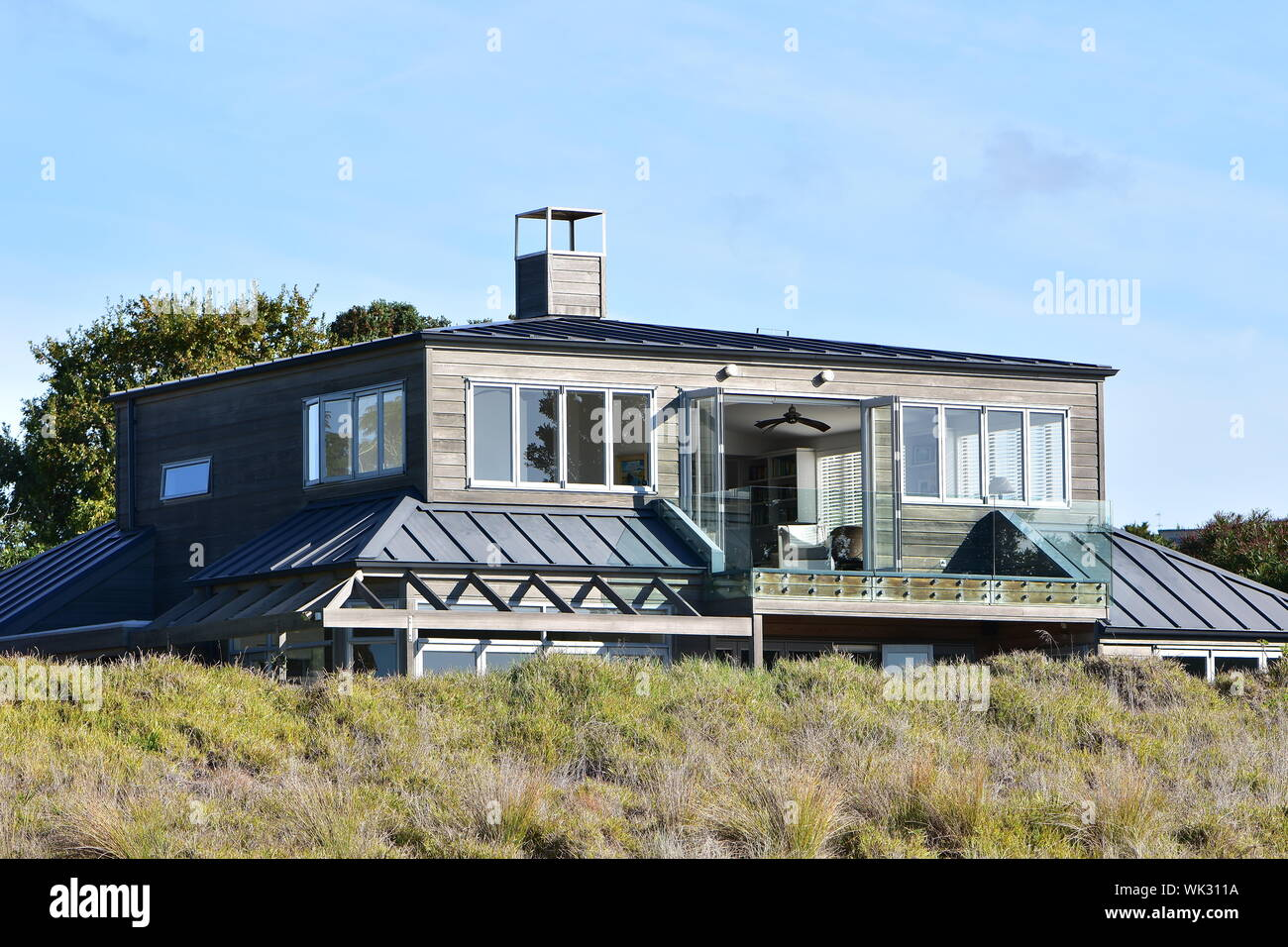 Modern wooden house protected from wind by dune yet allowing good views from upper story. Stock Photo