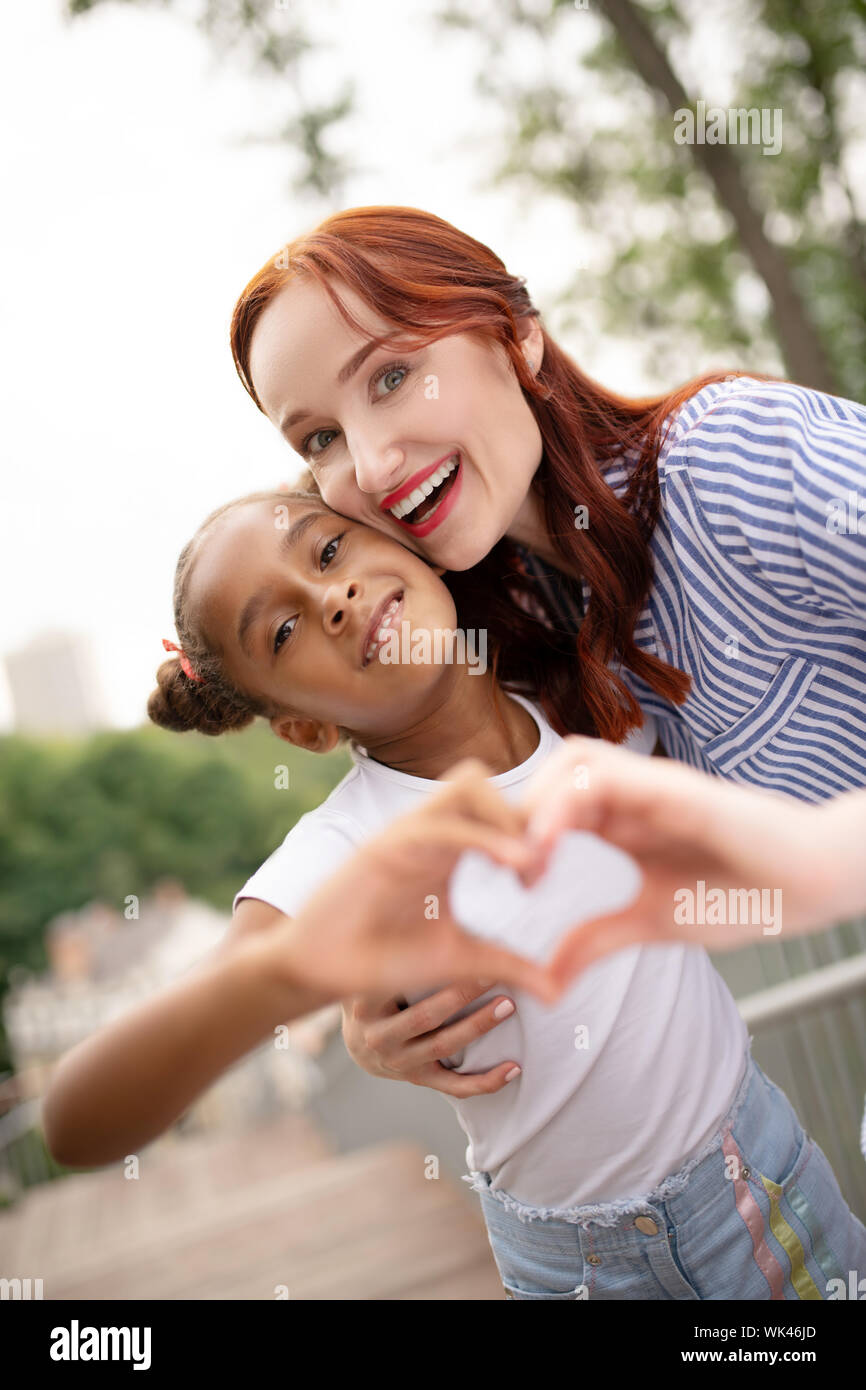 Red-haired woman with bright lips hugging her funny daughter Stock Photo