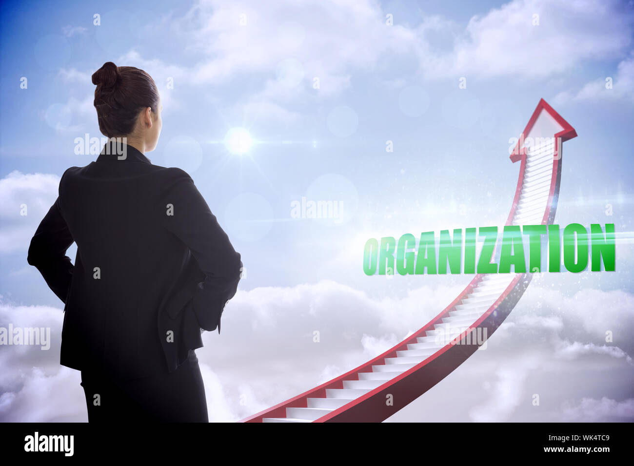 The word organization and businesswoman with hands on hips against red stairs arrow pointing up against sky - Stock Photo