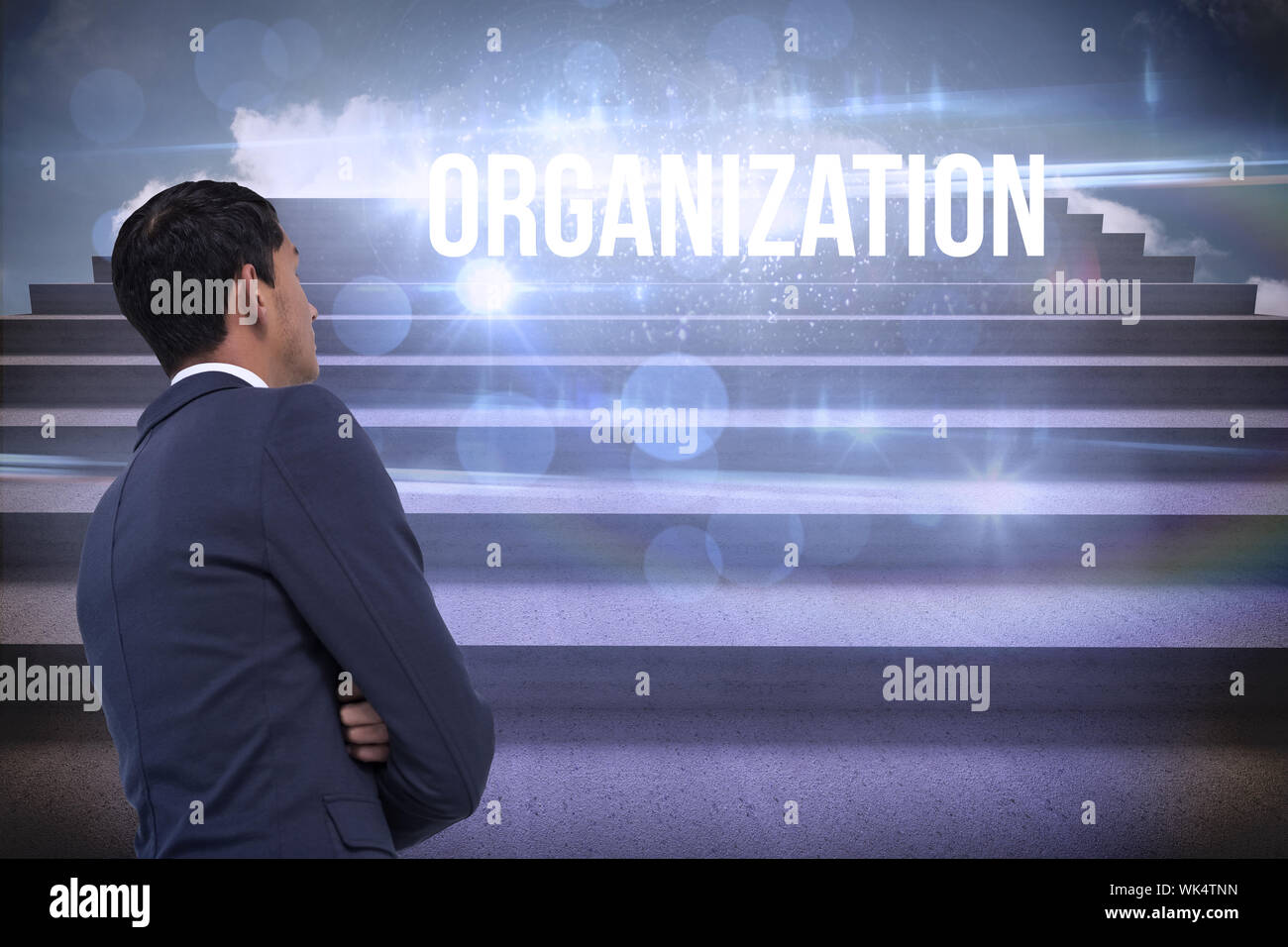 The word organization and unsmiling asian businessman with arms crossed against steps against blue sky - Stock Photo