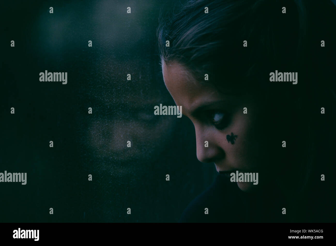 young little girl with dark makeup for Halloween holiday party looking on her reflection in window lit buy movie greenish light Stock Photo
