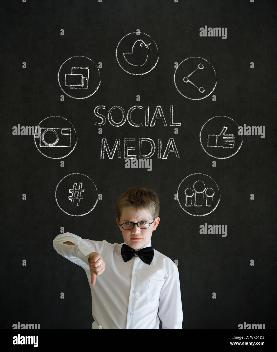 Thumbs down boy dressed up as business man with social media icons on blackboard background Stock Photo