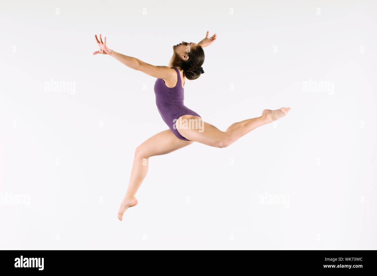 Young Gymnast Mid-air during Jump Stock Photo