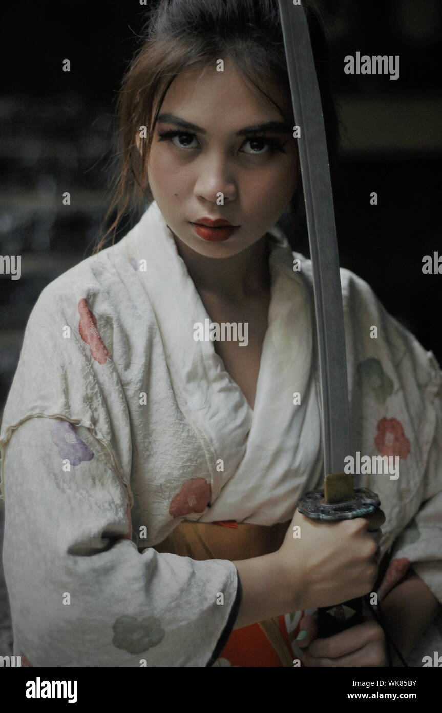 Portrait Of Young Woman Holding Sword Stock Photo