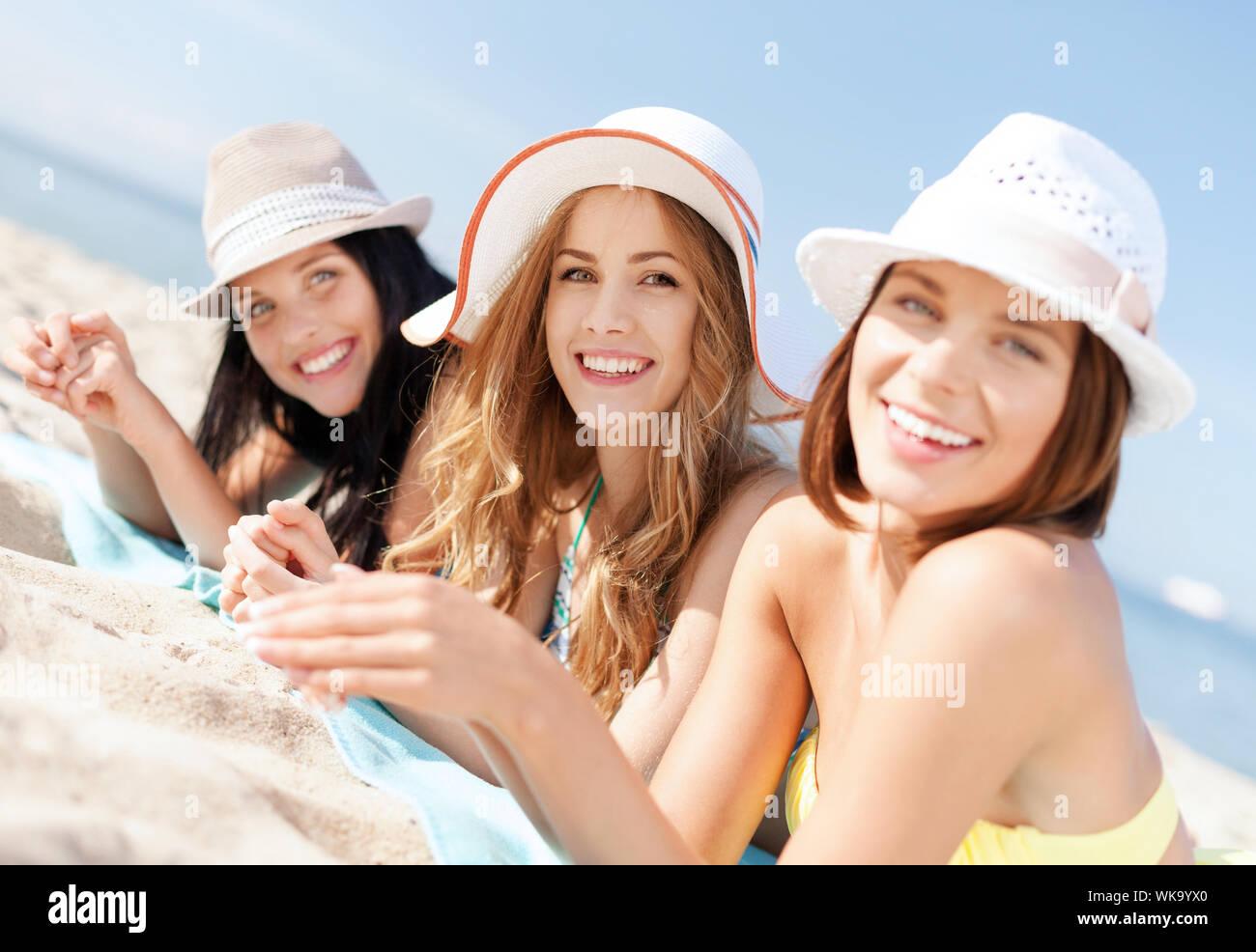 summer holidays and vacation - girls in bikinis sunbathing on the beach Stock Photo