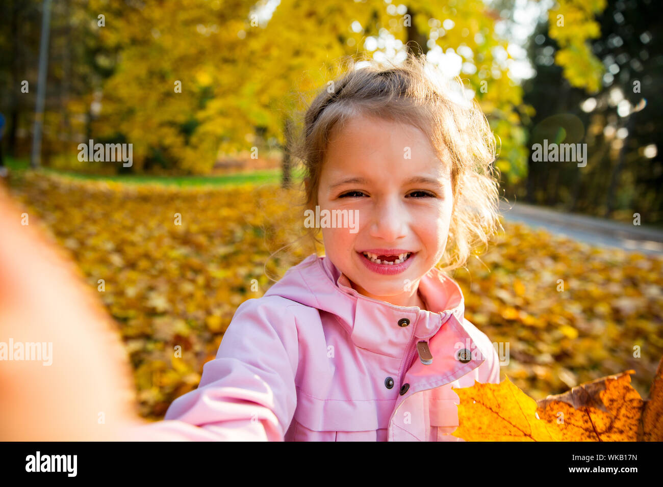 Cute little girl with missing teeth taking selfie. Happy child laughing and smiling. Sunny autumn forest, sun beam. Stock Photo