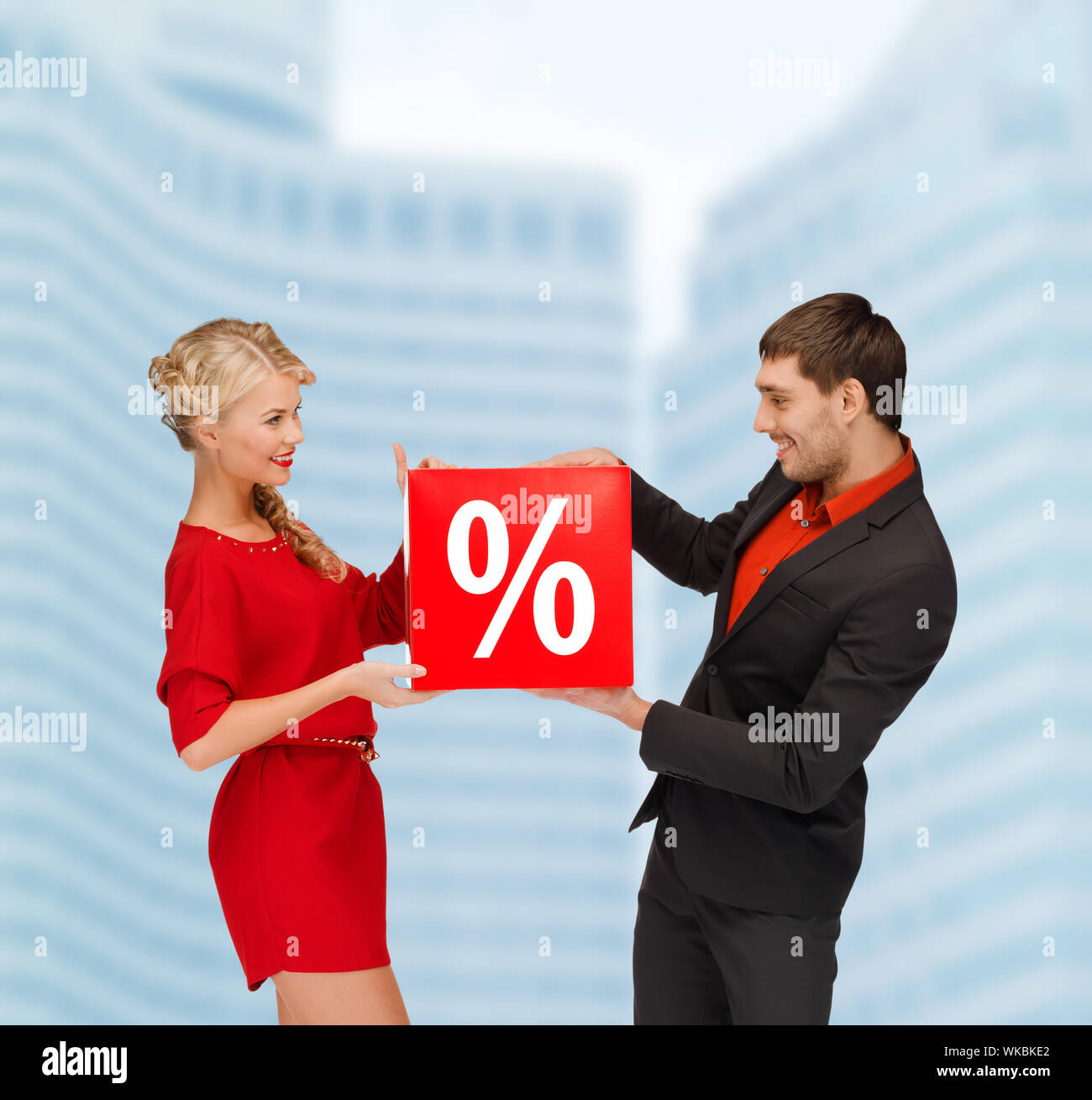 shopping, sale, christmas, couple and x-mas concept - smiling woman and man with red percent sale sign outdoors Stock Photo