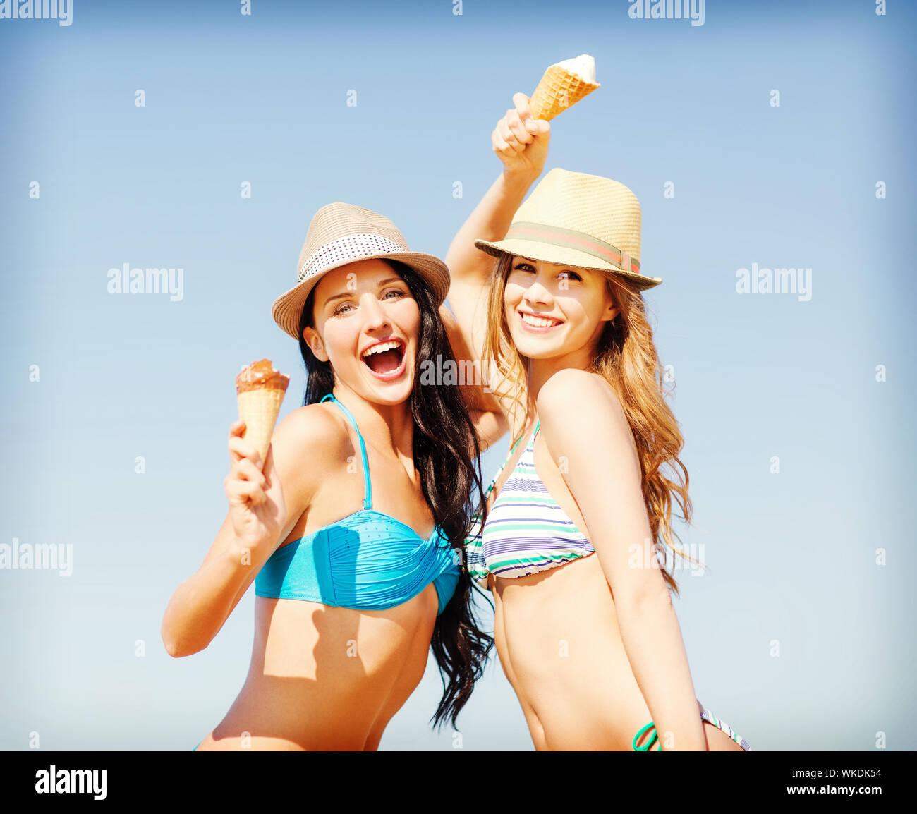 girls in bikini with ice cream on the beach Stock Photo