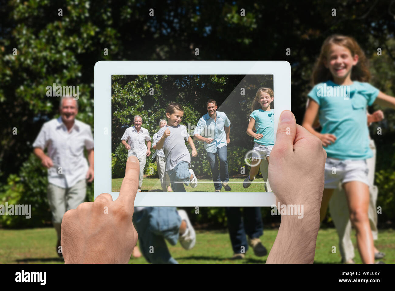 Hand holding tablet pc showing happy multi generation family racing towards camera Stock Photo