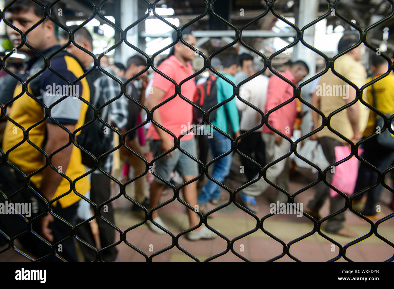INDIA, Mumbai, suburban railway station of commuter train Western Railway WR, commuter travel between suburbans and city centre, view from barred train window Stock Photo