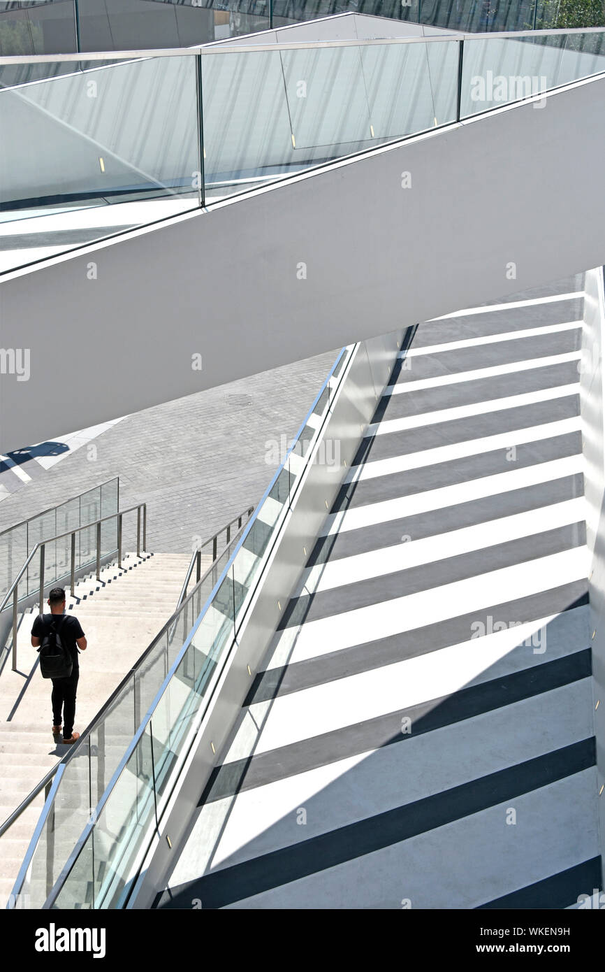 """Back view of man walking alone down steps from walkways & ramps at """"The Tide"""" a linear park of elevated walks above North Greenwich London England UK Stock Photo"""