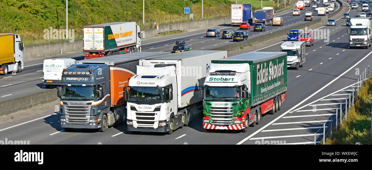 Supply chain hgv lorry truck drivers in cabs of articulated trailer vehicles overtaking in traffic lorries trucks busy four lane motorway England UK Stock Photo