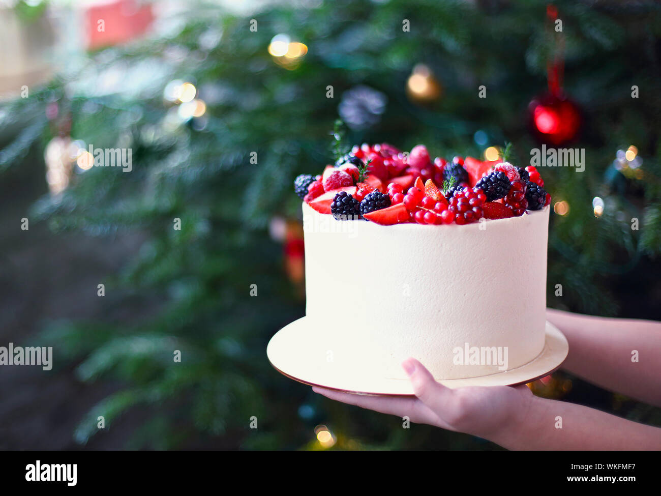 Woman holding Christmas Cake decorated with berries by the Christmas tree Stock Photo