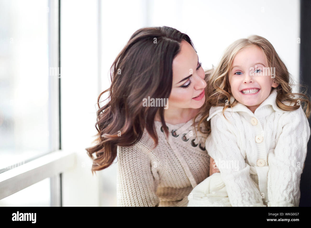 Happy loving family together. Mother and child daughter hugging by the window wearing cozy sweaters Stock Photo