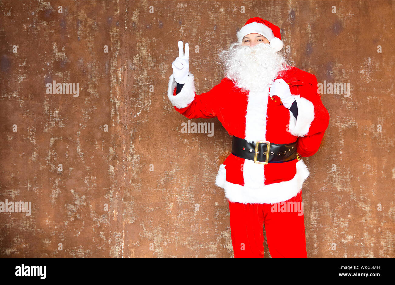 Santa Claus walking with the big red bag of the presents on the brown background Stock Photo
