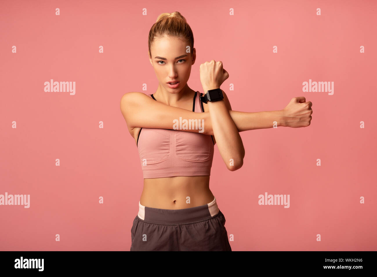 Young Lady Doing Arm Stretch Exercise On Pink Background Stock Photo