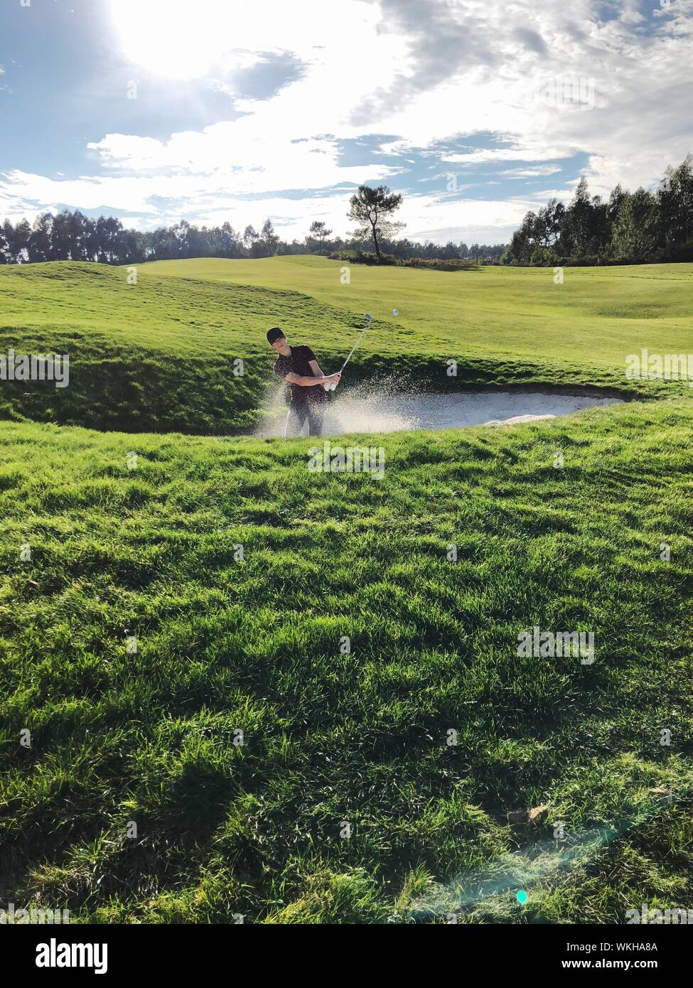 Man Playing Golf Against Sky Stock Photo