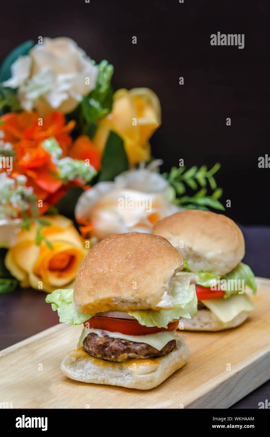Close Up Of Hamburgers On Cutting Board Against Bouquet Stock Photo Alamy