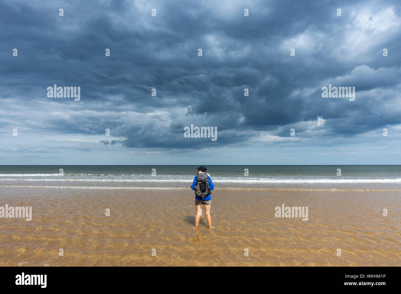Female hiker walking on beach under a stormy sky at Saltburn on the Yorkshire coast. UK Stock Photo