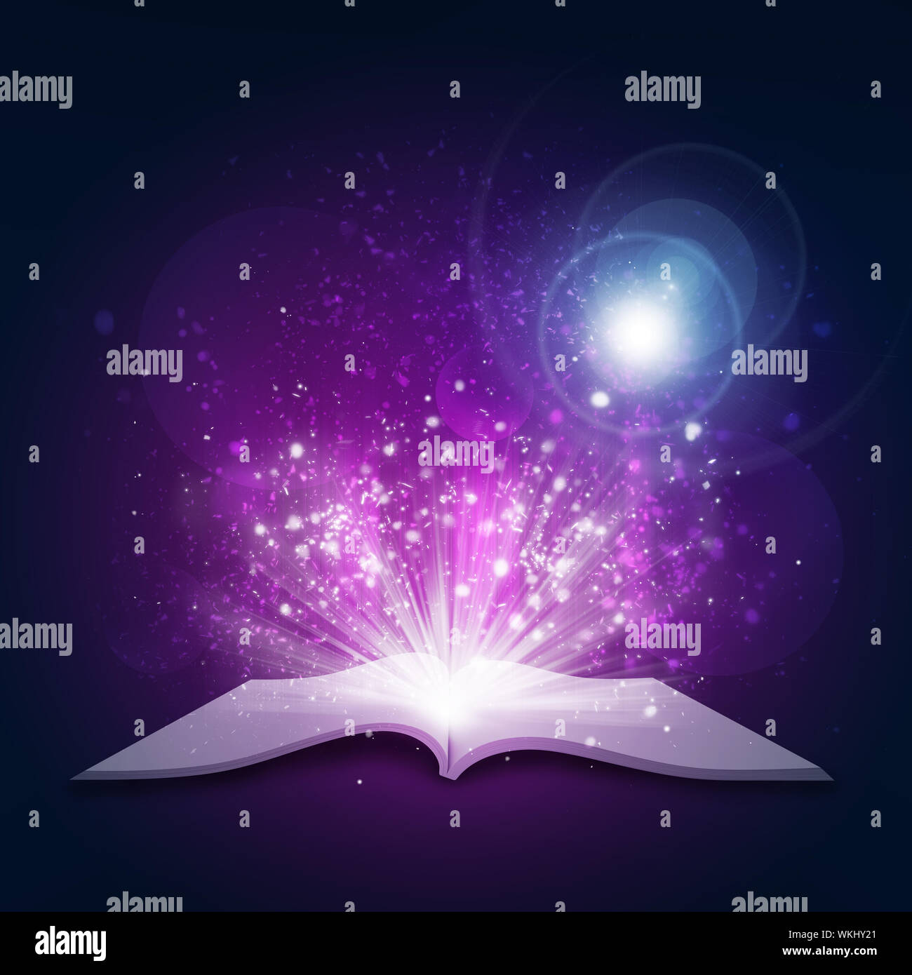 Old open book with magic light and falling stars. Dark background Stock Photo