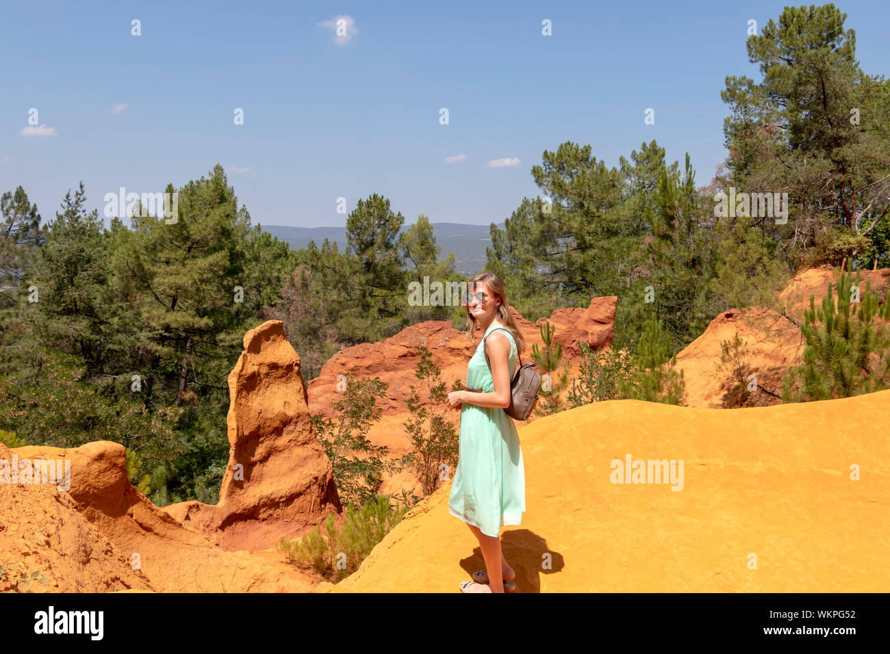 Young attractive blond caucasian woman, independent solo traveler in Ochre Trail in Roussillon, hiking path in Sentier des Ocres Stock Photo