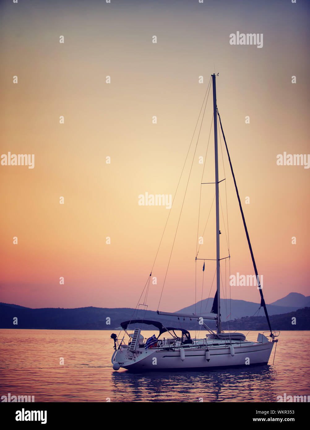 Luxury sailboat in the sea in beautiful sunset light, interesting summer adventure, romantic date on the water, travel and tourism concept Stock Photo