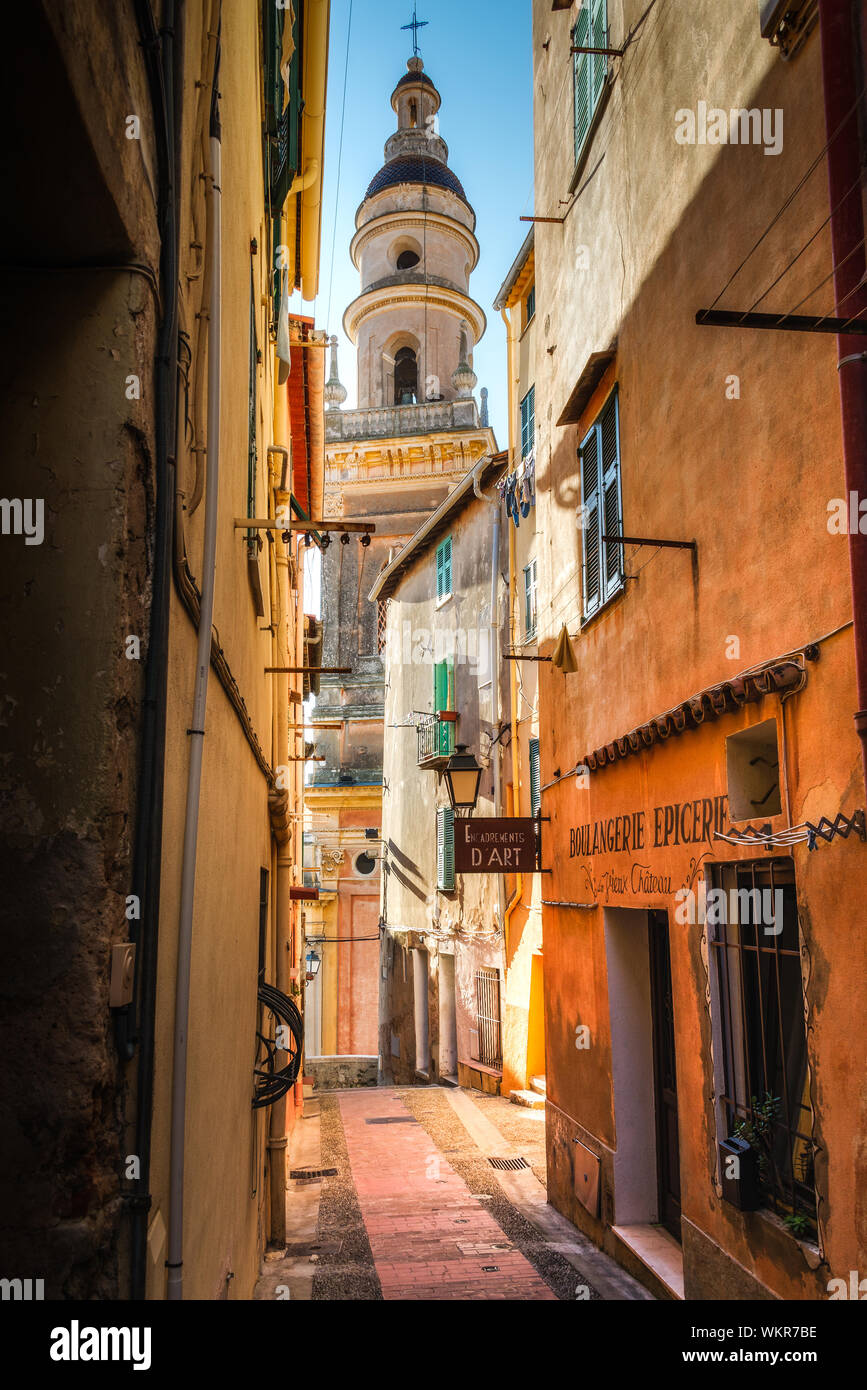 Colourful, narrow twisting street, with view to church spire in Menton France. Stock Photo
