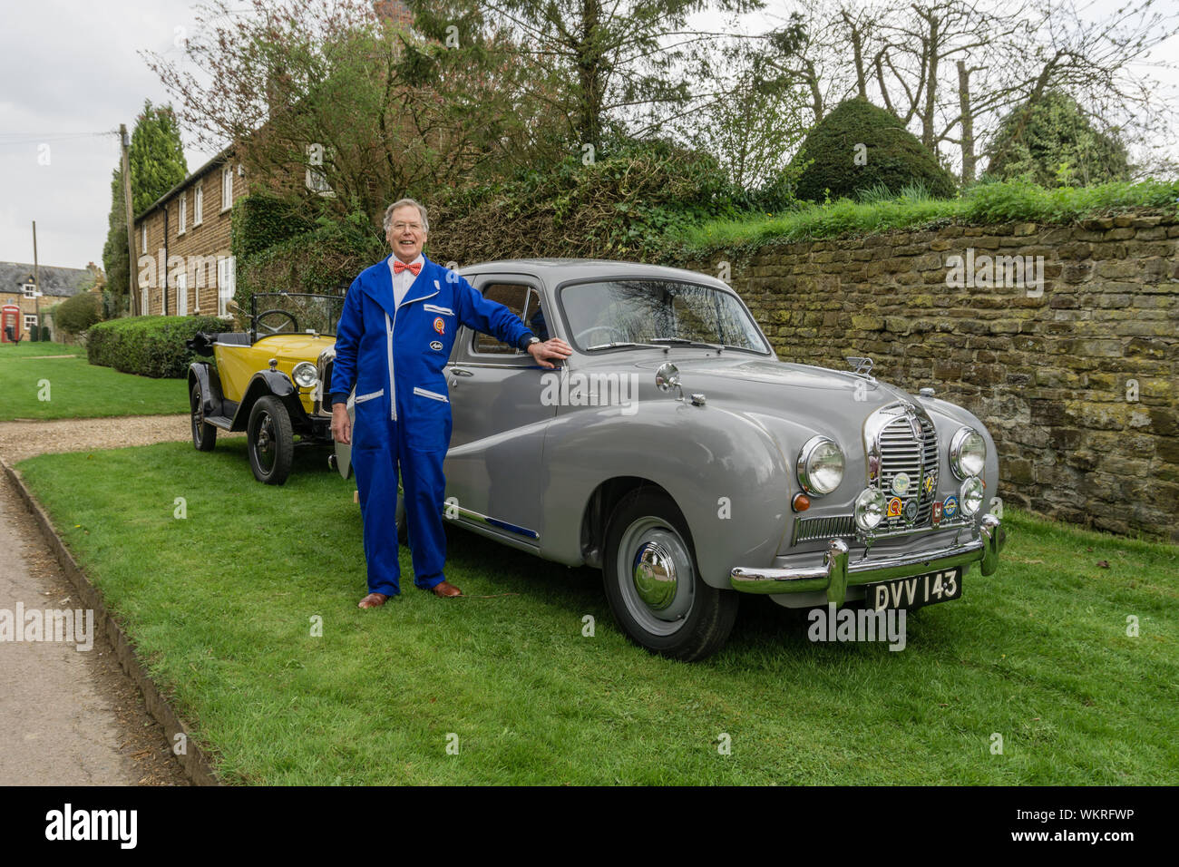 Car enthusiast, in made to measure blue overalls, poses in front of his vintage Austin saloon, Litchborough, UK Stock Photo