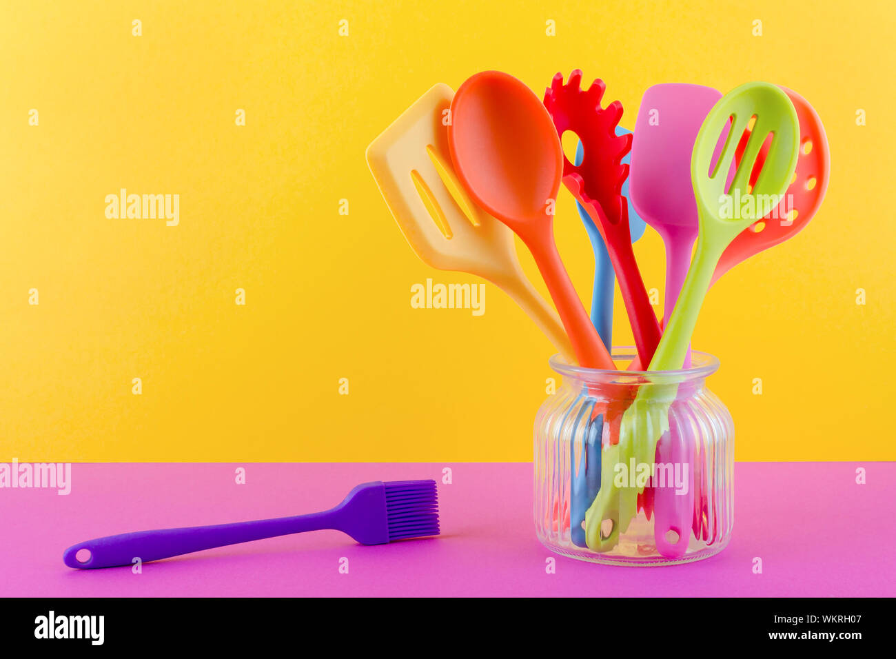 bright multi colored kitchen utensils on yellow background ...