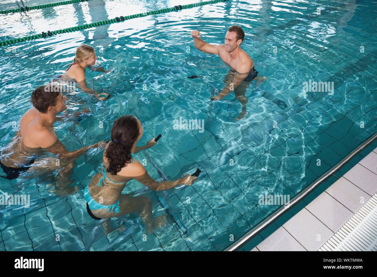 Fitness class doing aqua aerobics on exercise bikes in ...