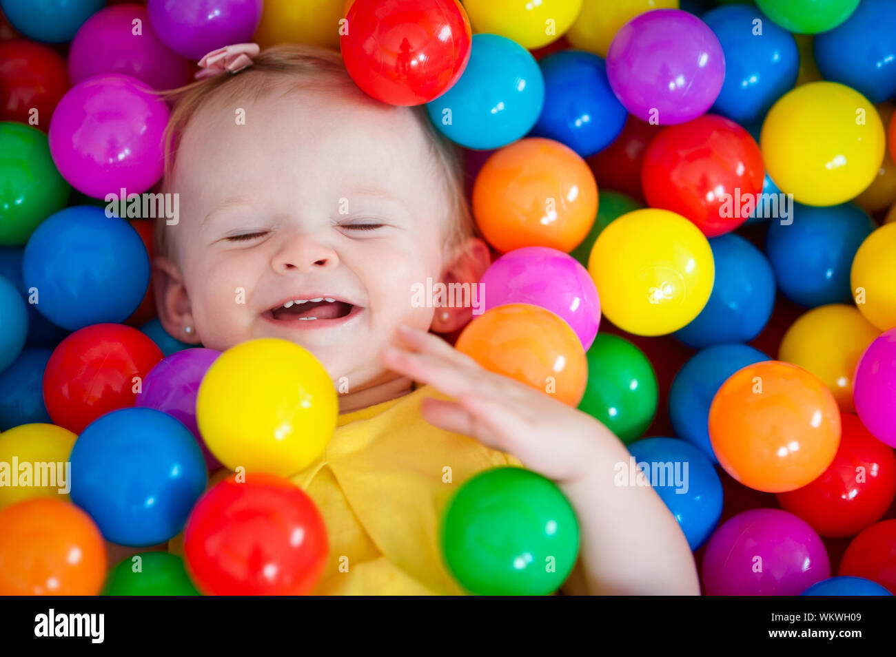 Horizontal close-up portrait of a 13 months old baby girl playing and laughing with eyes closed inside a ball pit tent at home. Stock Photo