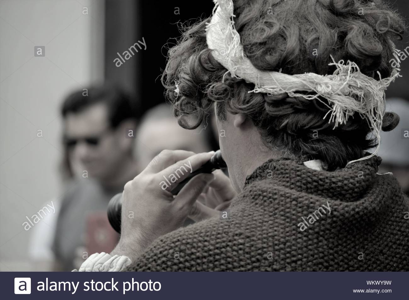Funny guy wearing a brown wig and  playing music with a flute on the street Stock Photo